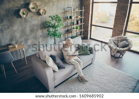 High angle view photo of amazing blond adorable aged granny good mood sitting comfy sofa divan reading favorite historic novel book nice free time living room indoors
