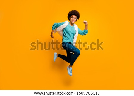 Full size photo of crazy funny funky afro american girl jump run hurry wear white turquoise sweater autumn blue stylish trendy outfit isolated over bright yellow color background #1609705117