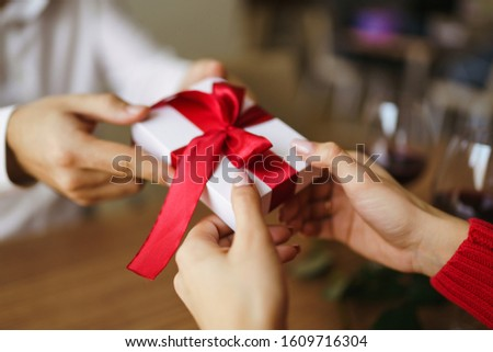 Man gives to his woman a gift box with red ribbon. Hands of man gives surprise gift box for girl. Young loving couple celebrating Valentine's Day.  Relationship, surprise, Birthday concept. #1609716304