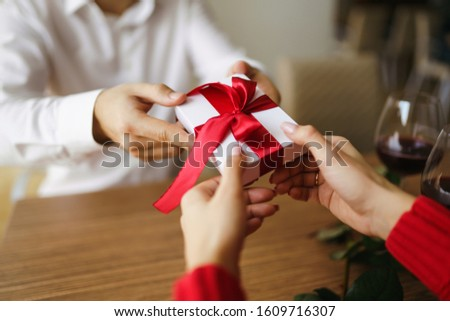 Man gives to his woman a gift box with red ribbon. Hands of man gives surprise gift box for girl. Young loving couple celebrating Valentine's Day.  Relationship, surprise, Birthday concept. #1609716307