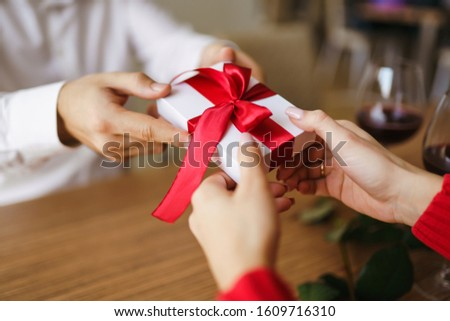 Man gives to his woman a gift box with red ribbon. Hands of man gives surprise gift box for girl. Young loving couple celebrating Valentine's Day.  Relationship, surprise, Birthday concept. #1609716310