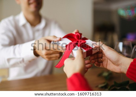 Man gives to his woman a gift box with red ribbon. Hands of man gives surprise gift box for girl. Young loving couple celebrating Valentine's Day.  Relationship, surprise, Birthday concept. #1609716313