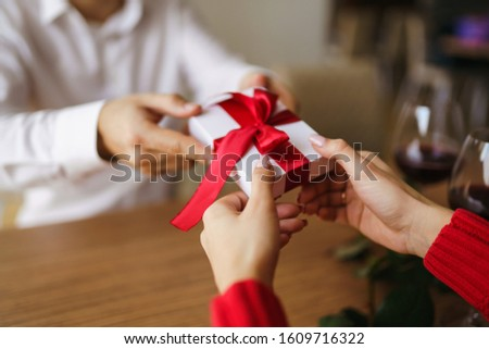 Man gives to his woman a gift box with red ribbon. Hands of man gives surprise gift box for girl. Young loving couple celebrating Valentine's Day.  Relationship, surprise, Birthday concept. #1609716322