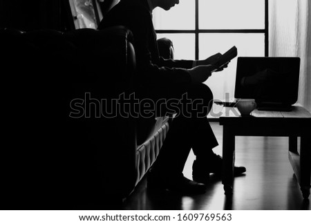 black silhouette of a man with a book,black silhouette of a man with a laptop,  black silhouette of a man in a chair against the window #1609769563