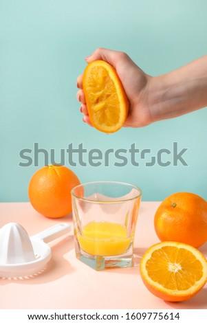 Creative and fashionable photo, pastel colors. Female hand crushes orange, juice. #1609775614