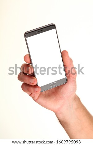 Human hand holds a modern smartphone with a blank chromakey screen in a palm. Technology and advertising concept. Detailed closeup studio shot isolated on abstract blurred white background #1609795093