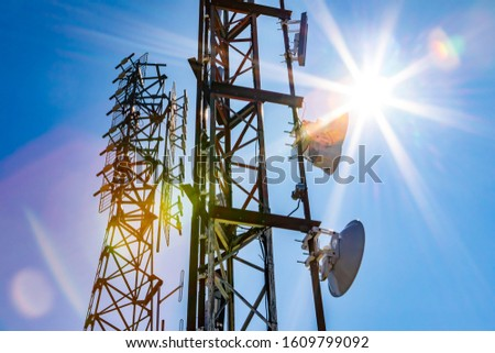 Bright sun shine over two cell site towers, radio and GPS transmitter and receiver, associated with electromagnetic pollution, with vibrant lens flare Royalty-Free Stock Photo #1609799092
