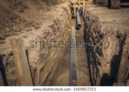 Construction site of an underground oil and gas pipeline.Work of burying oil and gas supply pipeline.work on the pipe laying of the pipelines in a special corrosion-resistant insulation in the trench #1609827211