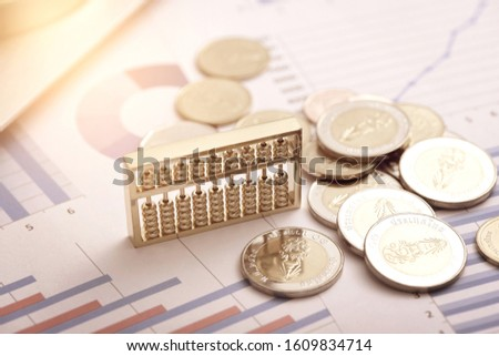 Abacus and coins on data drawings -- monetary and financial concepts #1609834714