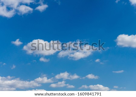A group of fluffy white clouds on a bright blue sky. #1609841791