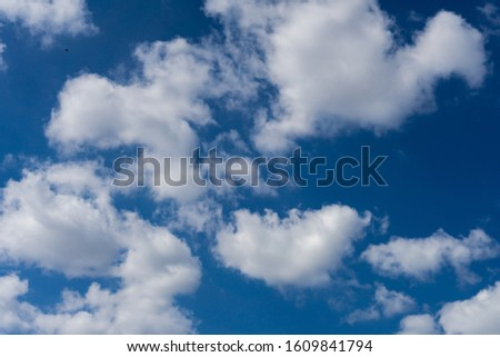 A group of fluffy white clouds on a bright blue sky. #1609841794