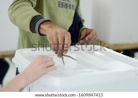 Person hand putting vote in a ballot box. Voters on election day.  Citizens casting their votes. People go to the polls. Presidential and parliamentary elections.  #1609847413
