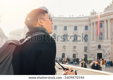 Young Asian man tourist taking photos with camera in hands near Hofburg palace in Vienna, Austria, Europe. Famous popular touristic place in Europe #1609870546