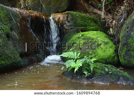 Water flows along the canals of the roadside, creating a small waterfall that is blurred #1609894768