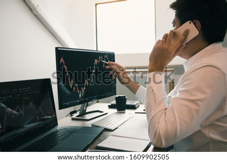 Agent trader man talking at telephone and checking business stock data on computer in office room. #1609902505