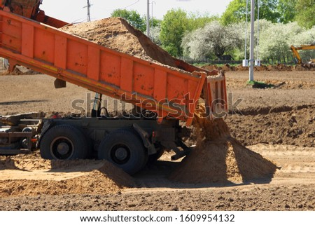 Heavy orange dumper truck unload sand from tailgate at the construction site on Sunny summer day #1609954132
