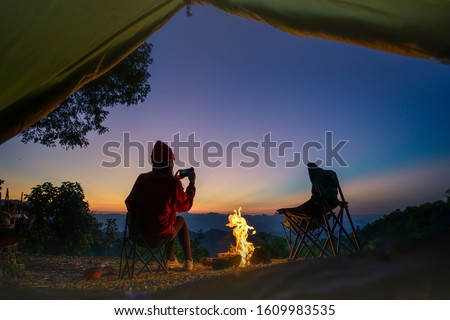 view from tent of woman traveller camping in campfire enjoy taking photo at the sunset