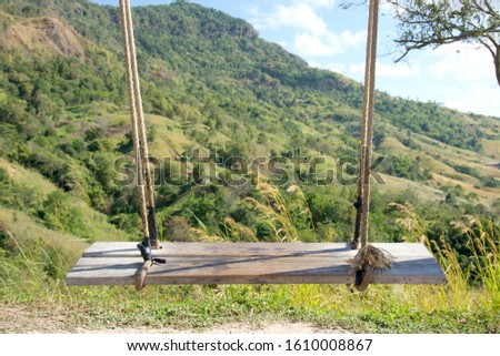 Wooden swing with rope swing, Behind the mountains and sky. Swings with no people sit. #1610008867