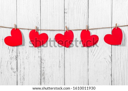 White painted wooden background with a garland of red hearts. Natural rope and clothespins. Concept of recognition of love, romantic relationships, Valentine's day in grunge style. Copy space #1610011930