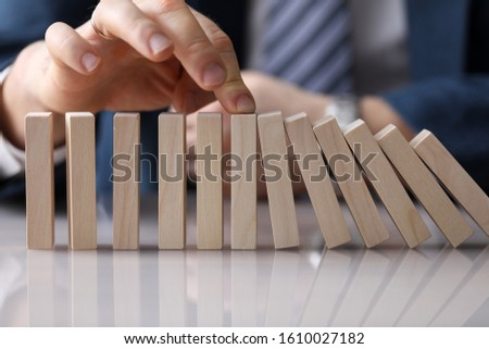 Close-up view of businessmans hand pushing wooden blocks placed in line on table. Falling identical same colour bricks. Business and strategy planning concept #1610027182