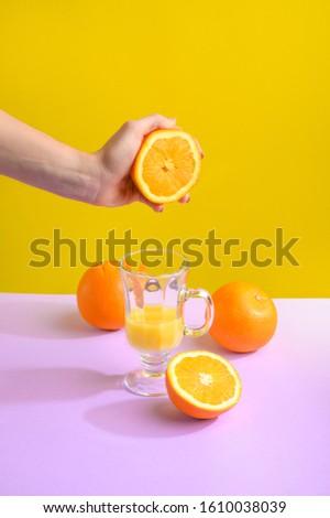 Female hand holding crushes orange and juice. #1610038039