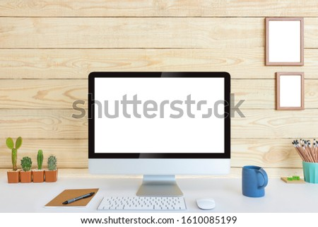 Computer with blank white copy space for text and wood background, Mockup design desktop computer in office on white table with keyboard and Coffee cub, Work place concept, Cactus in pot.
