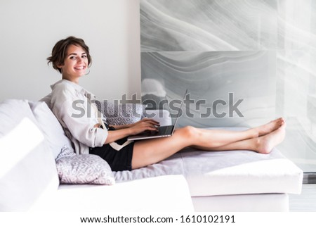 Happy woman working on a laptop sitting on the couch at home #1610102191