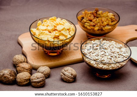 variations of cereals, raisins and walnuts on a decorative background #1610153827