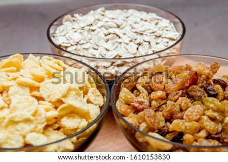 variations of cereals, raisins and walnuts on a decorative background #1610153830