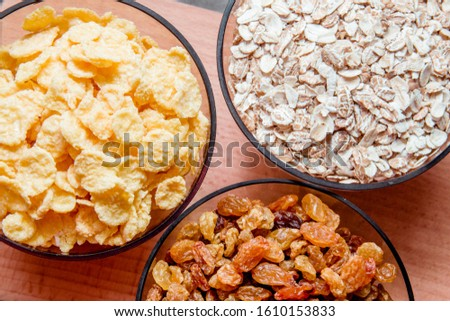 variations of cereals, raisins and walnuts on a decorative background #1610153833