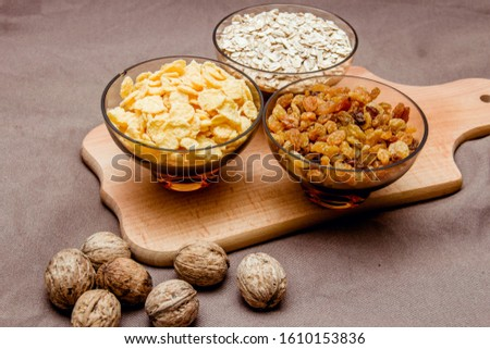 variations of cereals, raisins and walnuts on a decorative background #1610153836