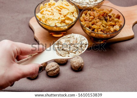 variations of cereals, raisins and walnuts on a decorative background #1610153839
