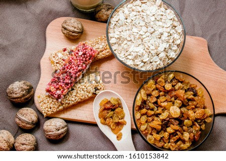 variations of cereals, raisins and walnuts on a decorative background #1610153842