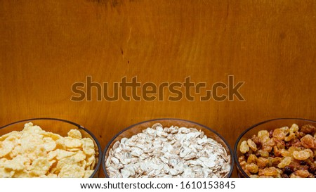 variations of cereals, raisins and walnuts on a decorative background #1610153845