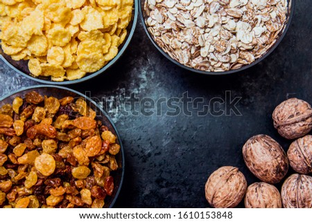 variations of cereals, raisins and walnuts on a decorative background #1610153848