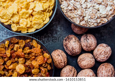 variations of cereals, raisins and walnuts on a decorative background #1610153851