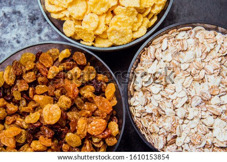 variations of cereals, raisins and walnuts on a decorative background #1610153854