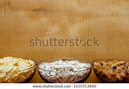 variations of cereals, raisins and walnuts on a decorative background #1610153860