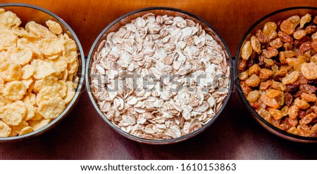 variations of cereals, raisins and walnuts on a decorative background #1610153863
