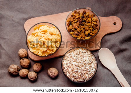 variations of cereals, raisins and walnuts on a decorative background #1610153872
