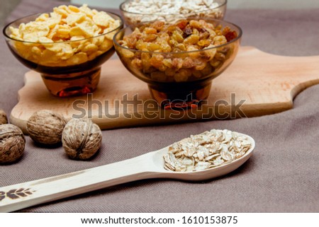 variations of cereals, raisins and walnuts on a decorative background #1610153875