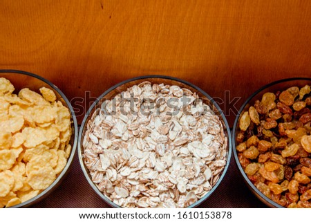 variations of cereals, raisins and walnuts on a decorative background #1610153878