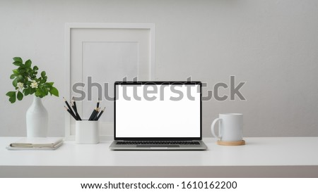Cropped shot of modern workspace with blank screen laptop, frame, pencils, coffee cup and vase on white table with white wall background     Royalty-Free Stock Photo #1610162200