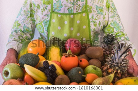 Front view of two hands holding a large wooden basket filled with freshly picked fresh fruit #1610166001