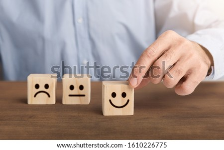 Customer service evaluation concept. The customers hand picked the happy face smile face symbol on wooden cube, copy space, panorama #1610226775