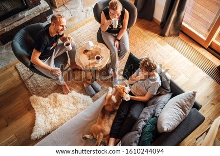 Cozy family tea time. Father, mother and son  at the home living room. Boy lying in comfortable sofa and  stroking their beagle dog and smiling. Peaceful family moments concept image. #1610244094