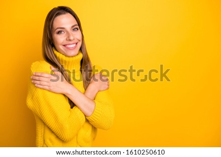 Turned photo of charming content girl hug herself enjoy warm knitted pullover isolated over yellow color background #1610250610
