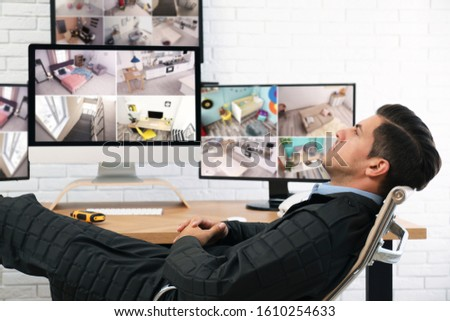 Male security guard resting near monitors at workplace #1610254633