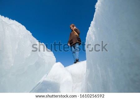 A woman on the background of broken ice covering the lake. #1610256592