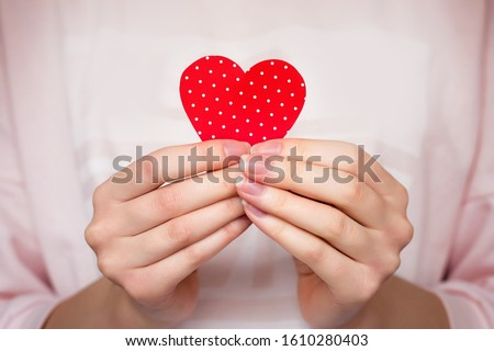 Girl holds a red heart in her hands, close up. Female hands holding a heart in her hands, Valentine's Day, love, romance background #1610280403